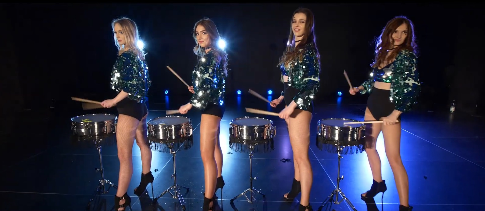 four girls in drum outfits playing on drums